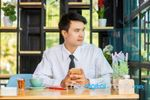 business-man-using-mobile-phone-while-sitting-in-the-coffee-shop-100562046.jpg